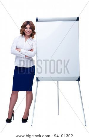 Full length portrait of a happy businesswoman standing with arms folded near blank flipchart isolated on a white background. Looking at camera