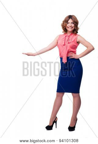 Full length portrait of a smiling woman demonstrating something isolated on a white background. Looking at camera