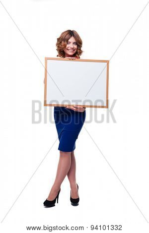 Full length portrait of a smiling woman holding whiteboard isolated on a white background. Looking at camera