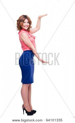 Full length portrait of a happy cute woman holding copyspace on palms isolated on a white background. Looking at camera