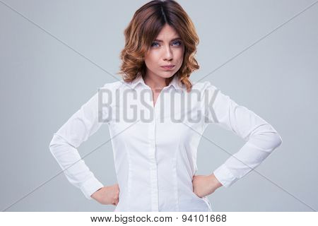 Portrait of a cute offended woman looking at camera over gray background