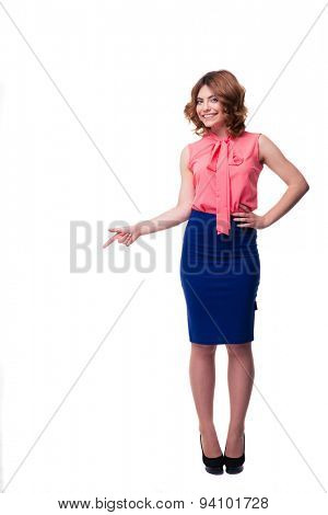Full length portrait of a happy woman pointing finger away isolated on a white background. Looking at camera