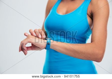 Closeup portrait of a woman using fitness tracker on wrist over gray background