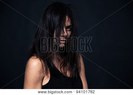 Portrait of exhausted woman looking at camera over black background