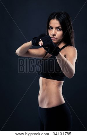 Fitness woman ready to fight over black background. Looking at camera