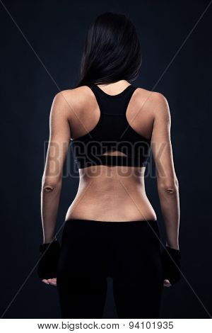 Back view portrait of a fitness woman in sports wear standing over black background