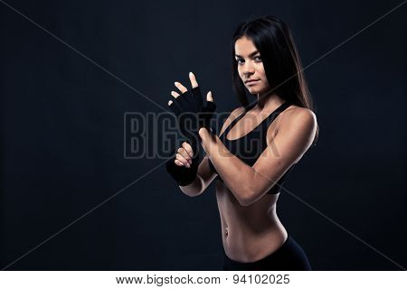 Portrait of a fitness woman standing over black background and looking at camera