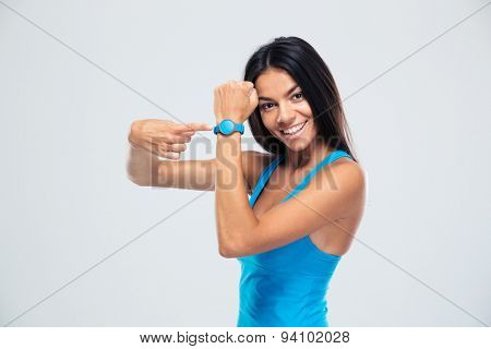 Smiling fitness woman pointing on fitness tracker over gray background