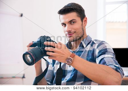 Happy man in casual cloth sitting at the table with photo camera