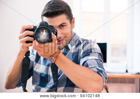Man in casual cloth shooting with photo camera