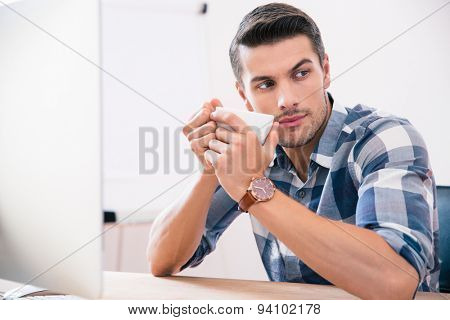 Handsome businessman sitting at the table and drinking coffee in office. Looking away