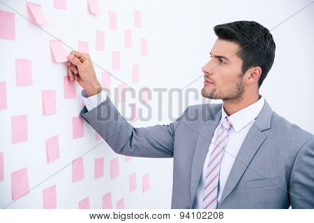 Handsome businessman looking on sticker at wall in office