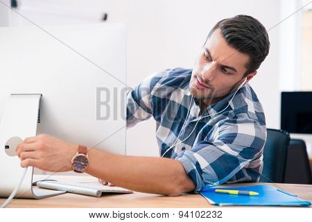 Businessman in casual cloth sitting at the table and connecting cord to computer
