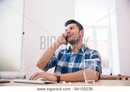 Happy businessman sitting at the table and talking on the phone in office