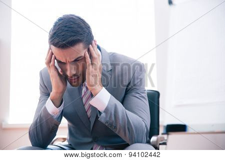 Pensive businessman sitting on office chair in office