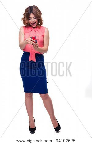 Full length portait of a happy casual woman opening gift box isolated on a white background