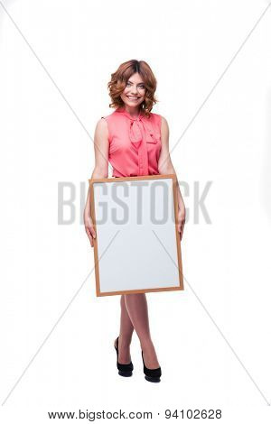 Full length portrait of a cheerful woman holding whiteboard isolated on a white background. Looking at camera
