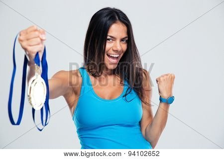Cheerful fitness woman with medal over gray background and looking at camera
