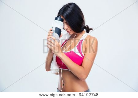 Fitness woman holding bottle with water over gray background