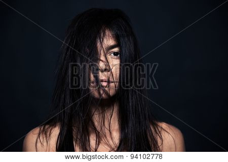 Portrait of tired woman standing over black background