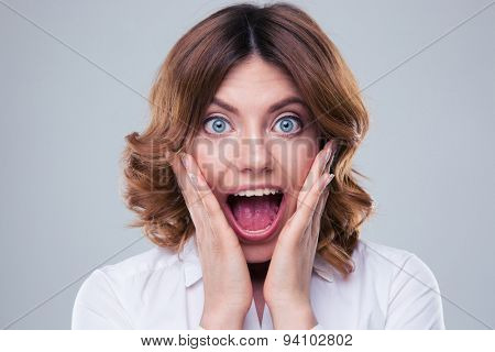 Scared face of woman over gray background. Looking at camera