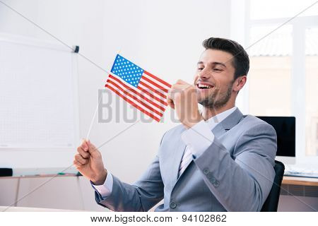 Cheerful handsome businessman holding USA flag in office