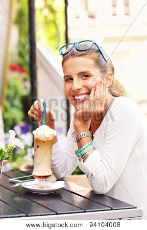 A picture of a happy woman drinking frappe in cafe