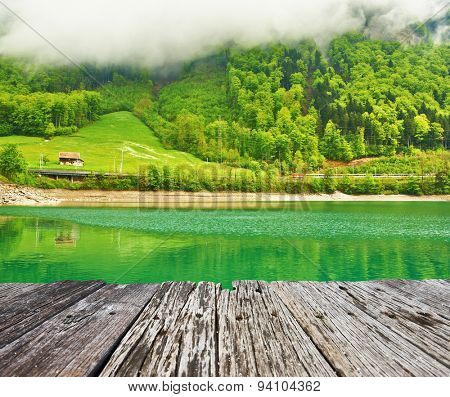 Beautiful emerald mountain lake in Switzerland under low clouds