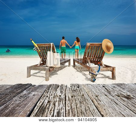 Couple in green relax on a tropical beach at Maldives