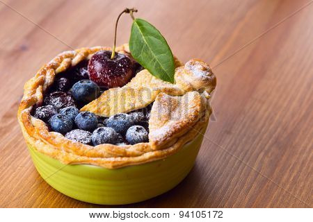 Decorated Homemade Shortcrust Pastry Berry Pie With Blueberries And Cherries In Green Ceramic Dish