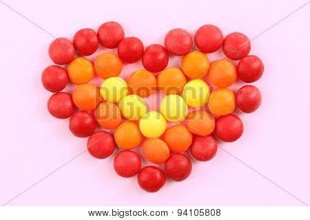 Sweet colorful candies in heart shape on pink background