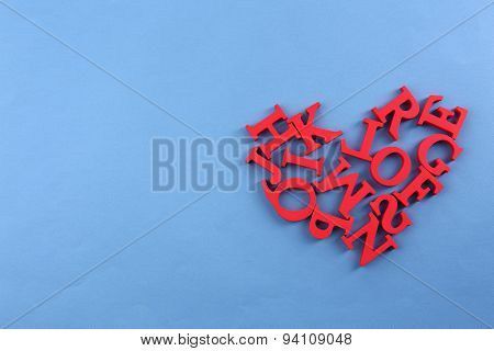 Red letters in heart shape on blue background