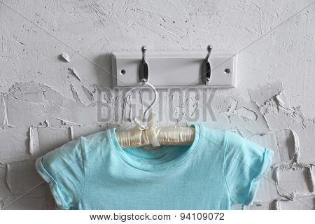 Child dress on hanger on white wall background