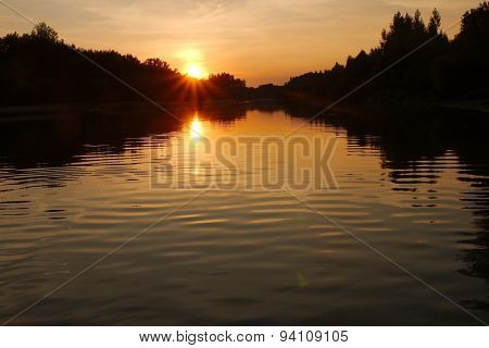 Setting sun in cloudy sky at the river