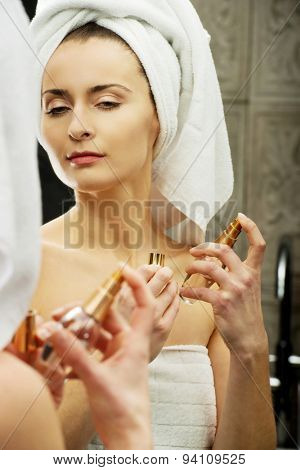 Attractive woman applying parfume in the bathroom.