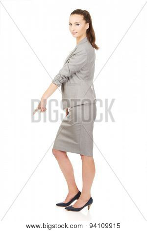 Beautiful confident businesswoman pointing down.