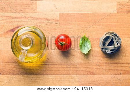 tagliatelle pasta with tomato and basil leaf on wooden table