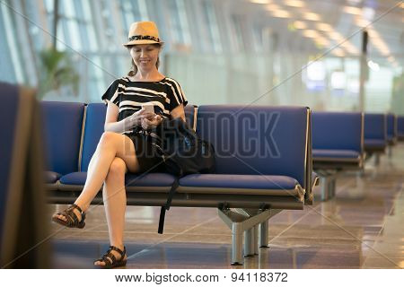 Woman Using Cellphone In Airport Waiting Lounge