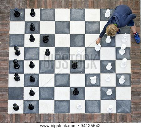 Young child making a move on an outdoor chessboard, seen from above