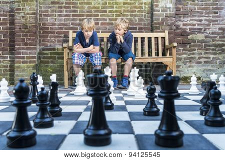 Two boys, sitting on a wooden bench, concentratedly thinking about their next move during an outdoors chess game with life sized pieces.