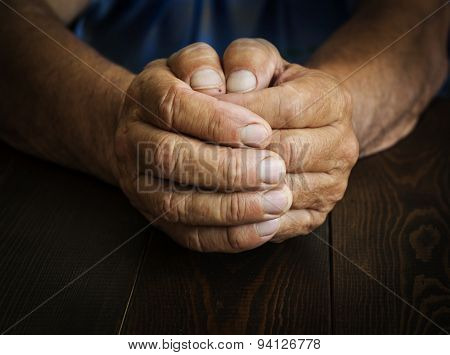Wrinkled hands elderly man at table