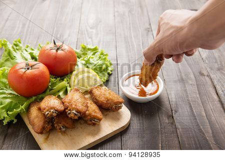 Hand Dunk Chicken Hot Wings In Dipping Sauce On Wooden.