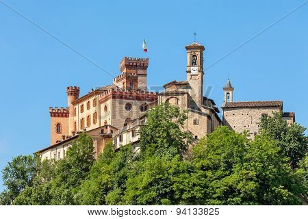 Medieval castle and church under blue sky in Barolo - small town in Piedmont, Northern Italy.