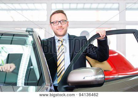 Salesman selling car at dealership