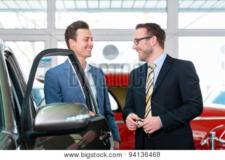 Man buying car in dealership and consulting salesman