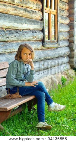 Portrait of ten-year old girl sitting on a bench near old village house