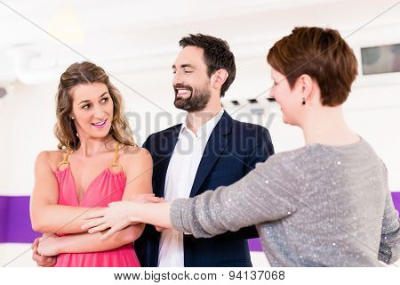 Instructor in dance school with couple of man and woman