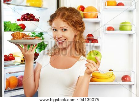 Woman On  Diet To Choose Between Healthy And Unhealthy Food Near Refrigerator