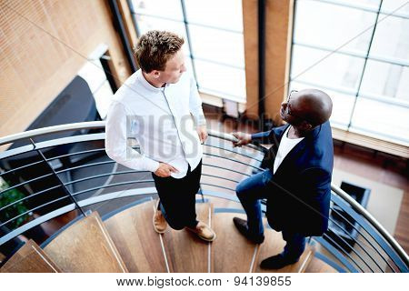 Colleagues Interacting At Work Standing On Staircase