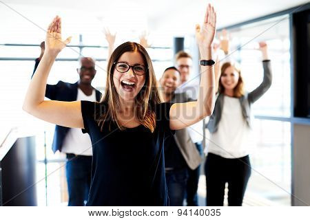 Female Executive Standing With Arms Up
